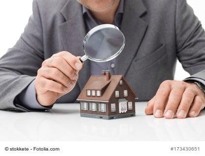 Modell eines Einfamilienhauses mit Lupe als Sinnbild für ein Wertgutachten für ein Haus