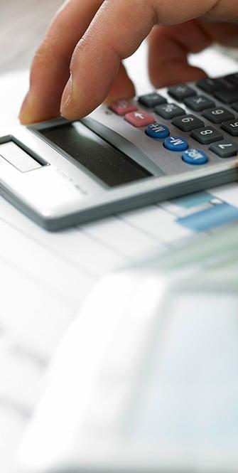 Foto von einem Taschenrechner auf einem Immobiliengutachten zur Verdeutlichung einer Auswertung von einer Immobilienbewertung.