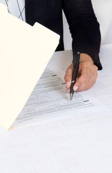 Gutachten im Papierfolder mit Hand zum Unterschreiben als Beispiel für Immobilienbewertung.