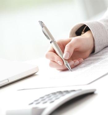 Foto von einer schreibenden Hand und Taschenrechner als Symbol für das Honorar bei einer Immobilienbewertung