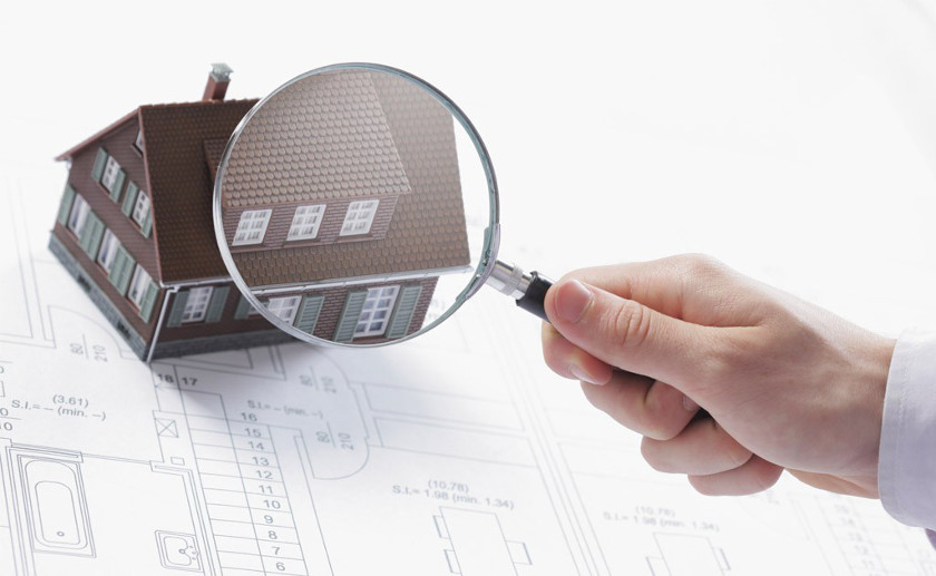 Modell eines Einfamilienhauses mit Lupe als Beispiel für ein Wertgutachten bei einem Haus