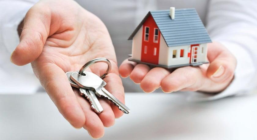 Linke Hand mit Modell Einfamilienhaus und rechte Hand mit Schlüsselbund als Symbol für eine Immobilienschätzung beim Hauskauf.
