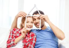 Paar schaut durch einen Zollstock in Hausform als Bezug zur Immobilienwertermittlung