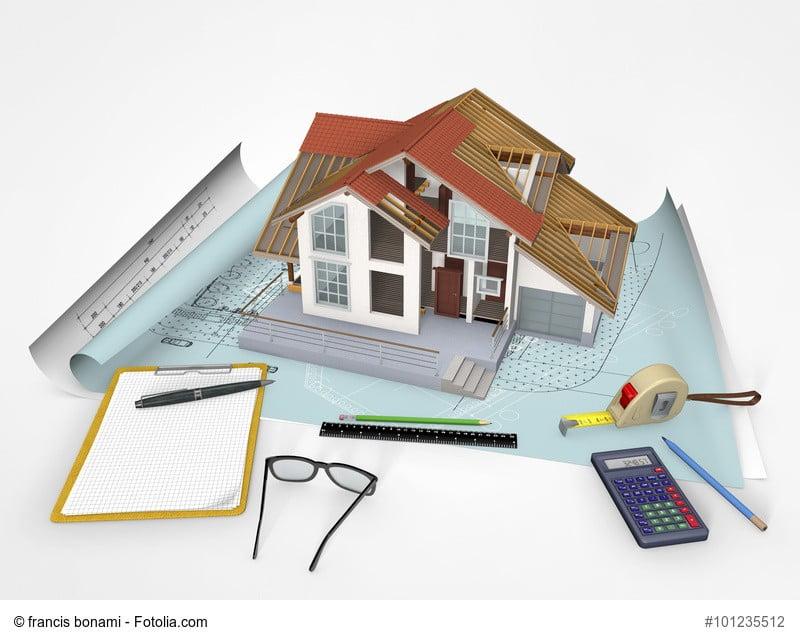 Grafik zeigt Modellhaus mit diversen Plänen, Taschenrechner und Messutensilien als Darstellung um einen Hauswert zu ermitteln