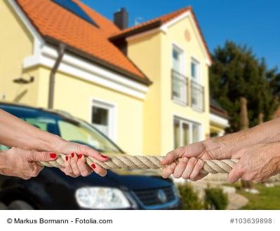 Tauziehen von Mann und Frau als Sinnbild für Gütertrennung bei einer Scheidung