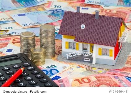 Geld, Rechner und Haus stellen die steuerliche Kosten einer Immobilie dar