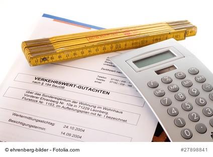 Gutachten mit Zollstock und Rechner als Symbol für die Ermittlung des Immobilienwertes durch Immobiliengutachter