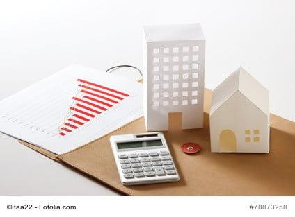 Symbolbild für das Ertragswertverfahren mit Taschenrechner, Chart und zwei Häusern