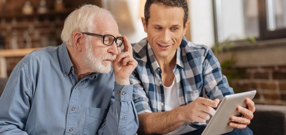 Vater und erwachsener Sohn besprechen die Eigentumsübertragung einer Immobilie im Rahmen einer Erbschaft oder Schenkung